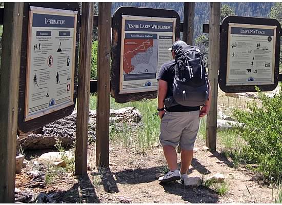 Mason, packed and ready to go, reading the information board near the trailhead.